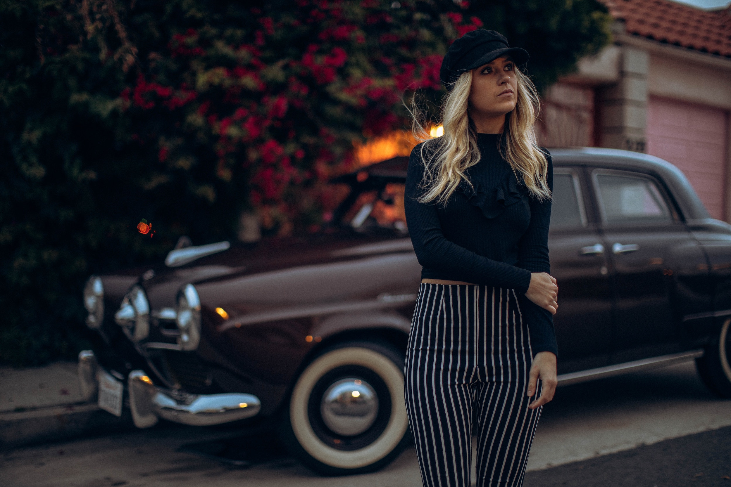 woman standing in street next to old car in pinstriped pants