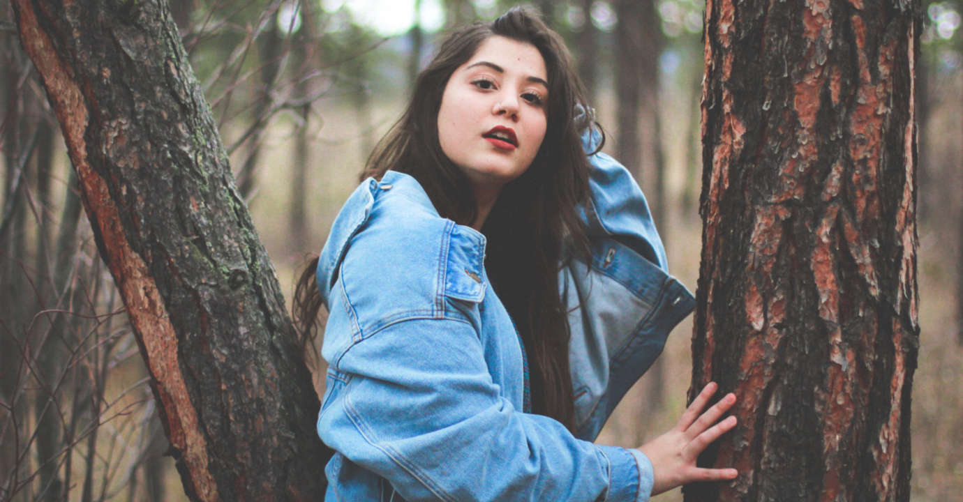woman in denim jacket leaning against tree